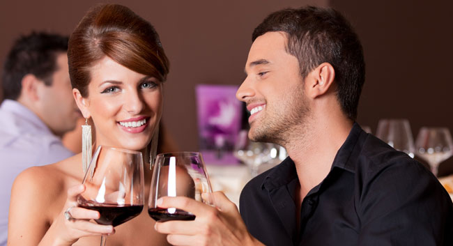 Love Stories - happy couple at restaurant table toasting